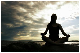 Woman doing yoga by ocean